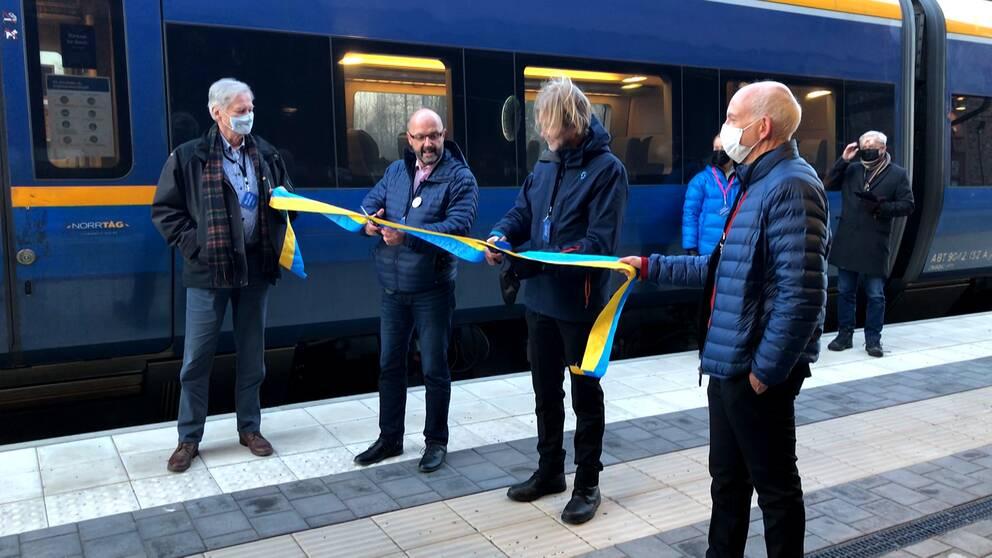 Fyra personer står vid ett band som ska klippas. I bakgrunden syns ett tåg.
