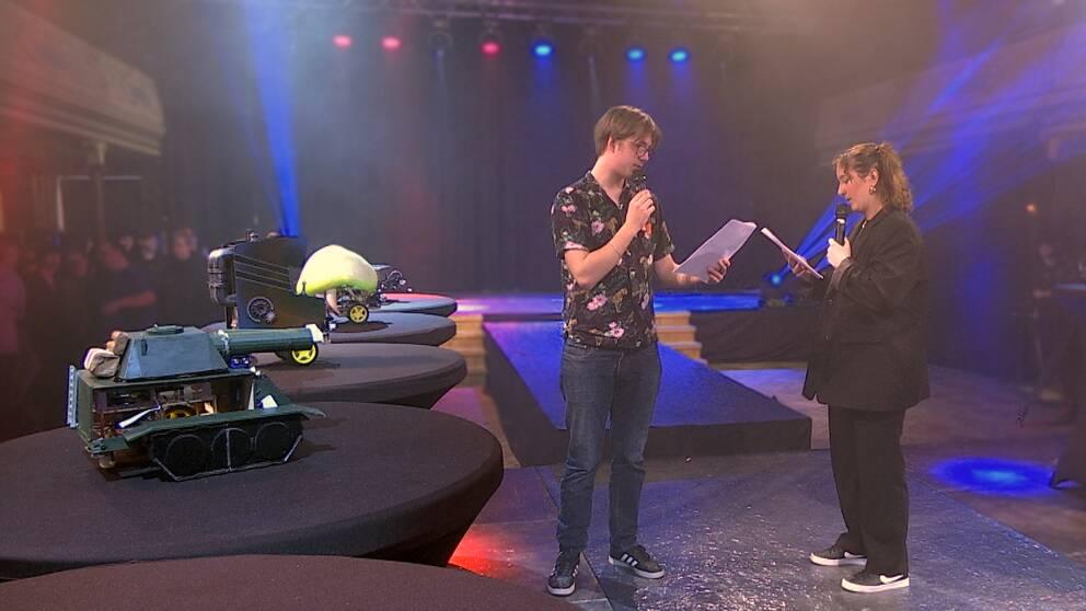 Två elever står på scenen med robotar