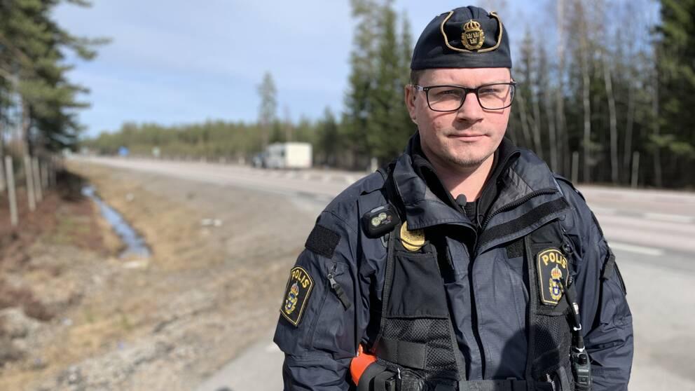 En manlig trafikpolis står vid sidan av motorväg E4 mellan Tönnebro och Gävle.
