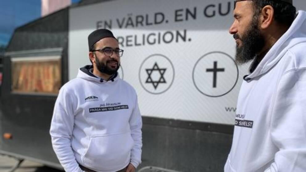 två imamer stående utanför sin turné husvagn