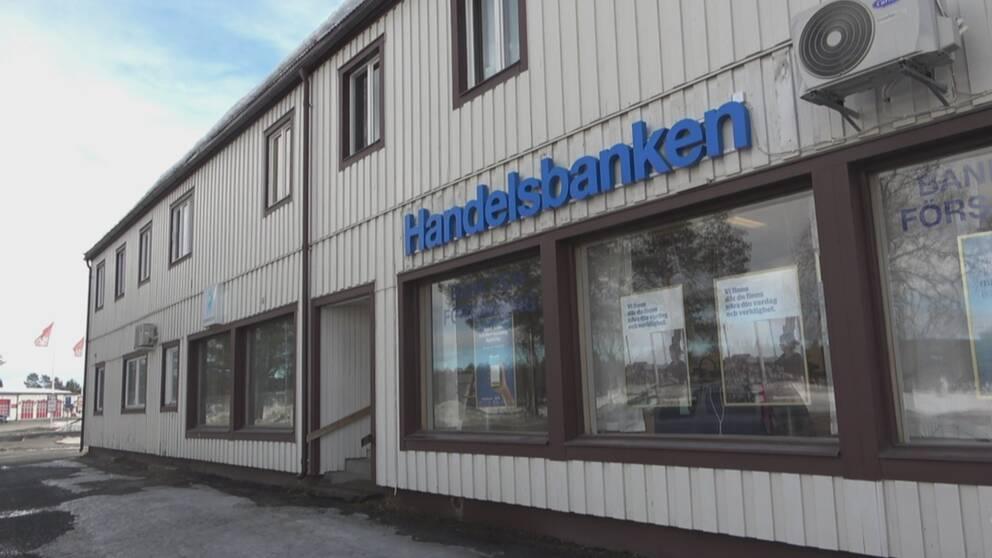 Husfasad med flera fönster och en blå skylt där det står Handelsbanken.
