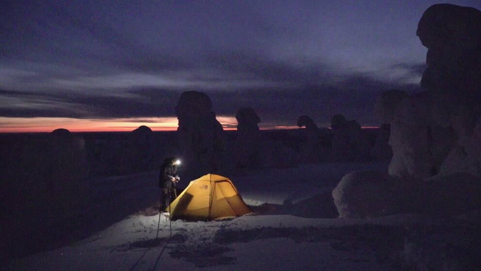 person med pannlampa står vid tält nattetid, träd inbakade i snö skymtar i mörkret