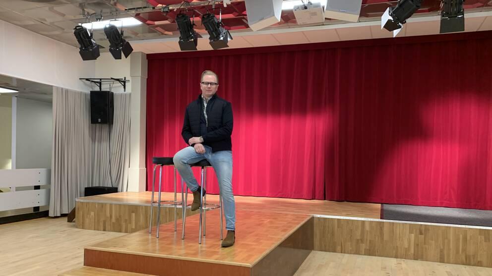 En man sitter på en stol på en scen