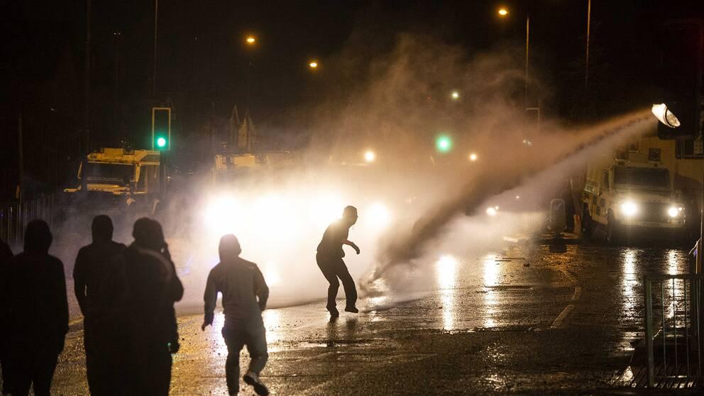 En vattenkanon skjuter en sotr stråle vatten mot svartklädda demonstranter i motljus. Våldsamheter bröt ut under torsdagen i västra Belfast när nationalistiska ungdomar attackerade polisen, som skingrade massorna med vattenkanoner.