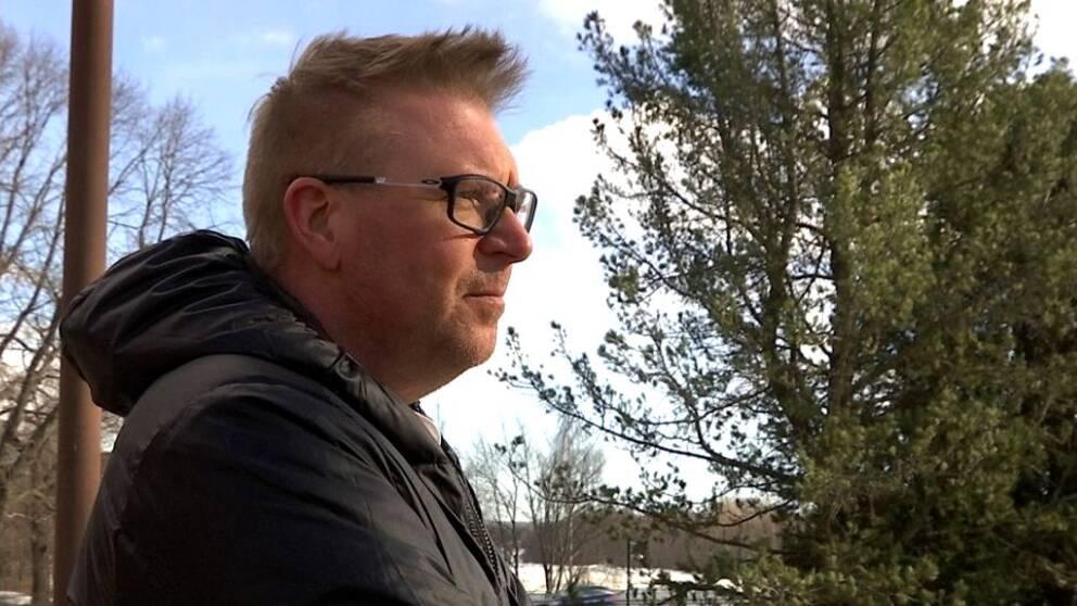 Michael Elfström – en man med glasögon och jacka ses i profil utomhus