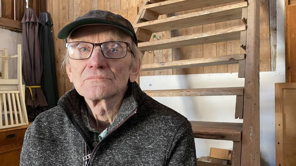 Sven-Erik Sjölund som driver auktioner i Ilsbo sitter på en trappa i en lada