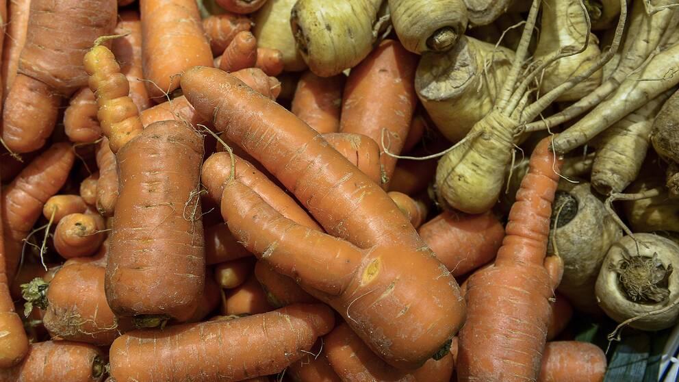 Morötter och palsternackor i en livsmedelsbutik.