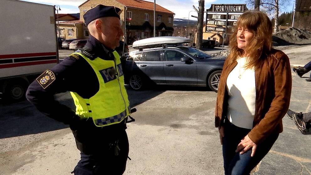 en man i poliskläder pratar med en kvinna på en parkering i Funäs