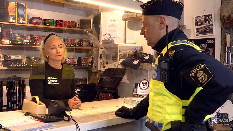 en kvinna bakom den kassadisk, goggles på hyllan bakom, samt en man i poliskläder som pratar med henne