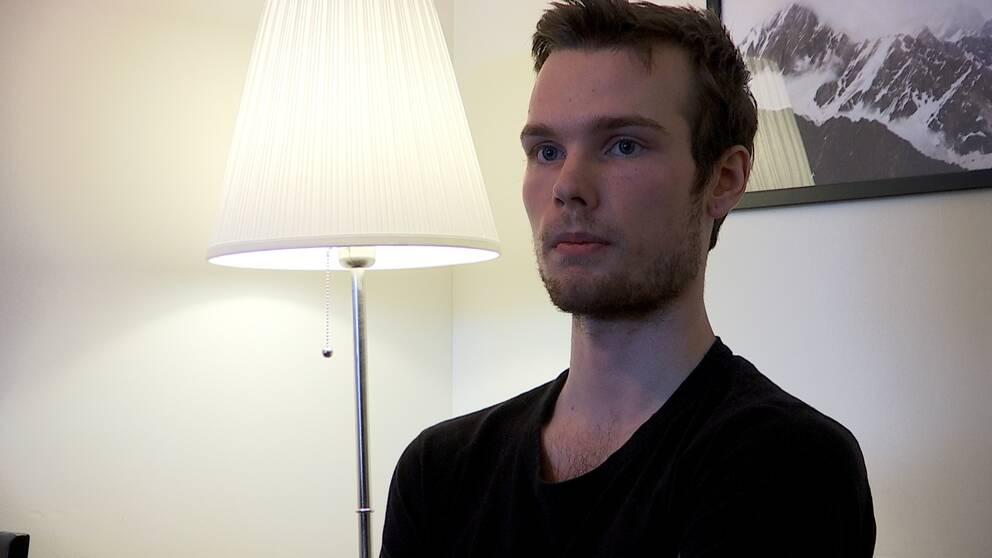 ung man som sitter bredvid en lampa i hemmiljö