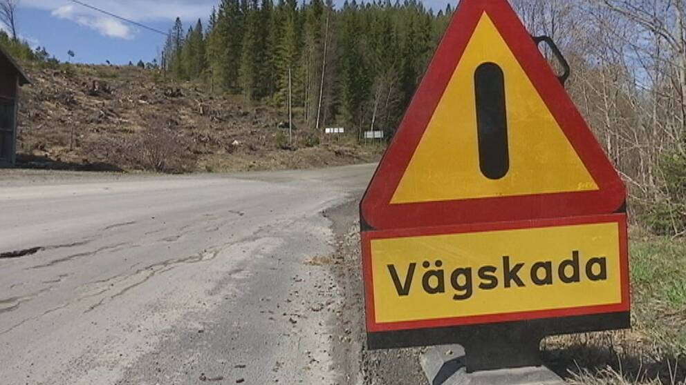 Bild på en dålig väg med en varningsskylt. Gul skylt med röd ram där det står vägskada.