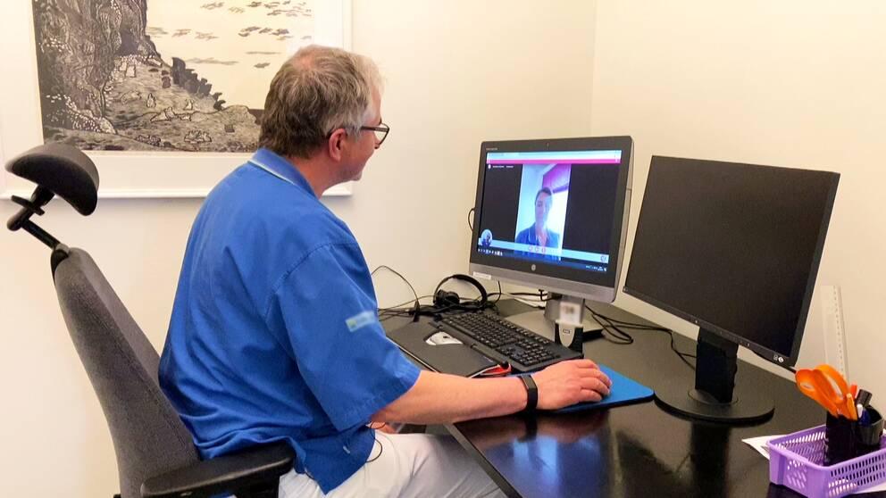 En man i blåa scrubs har ett digitalt möte framför en dator