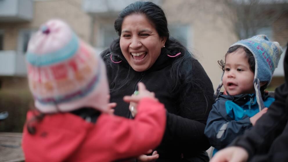 Ruth Acosta leker på innergården med sina tvillingar.
