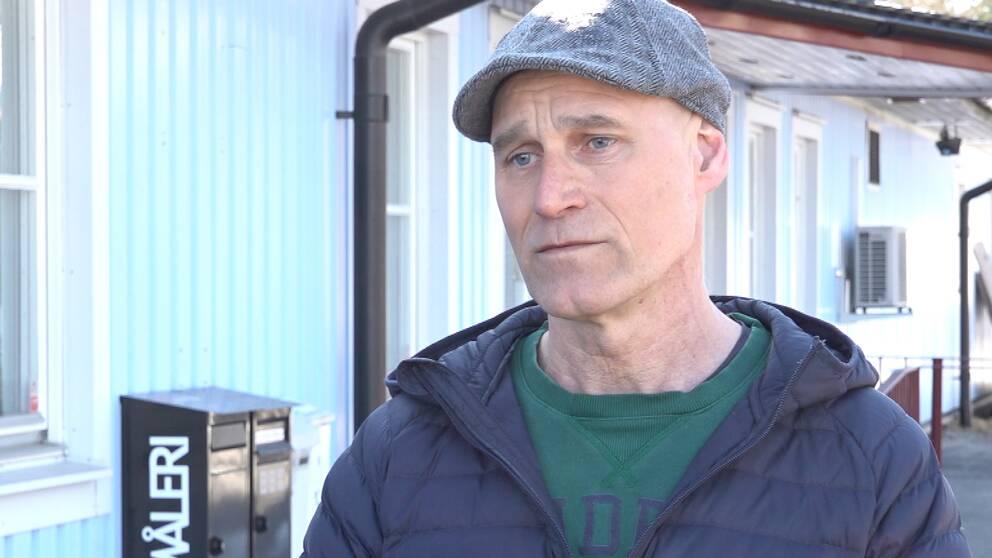"""en man i """"gubbkeps"""" och jacka intervjuas utanför ett trähus"""