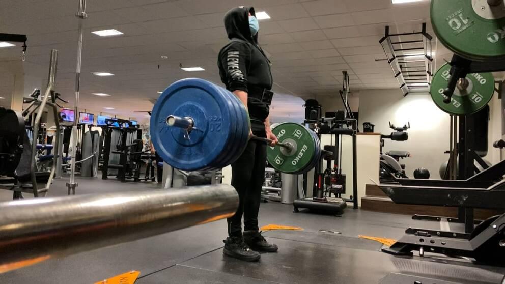 Samuel Johansson lyfter vikter, han väljer att bära munskydd på gym