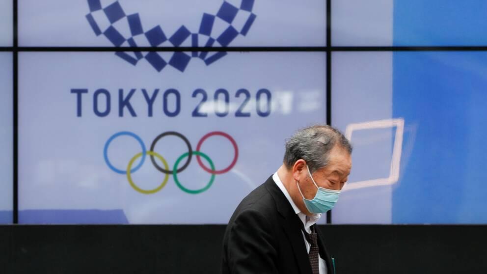 En förbipasserande man framför en av Tokyos OS-skärmar