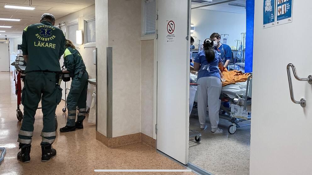 personal från ambulanshelikopter rullar in en brits i korridoren medan intensivvårdspersonal ses vårda en coronapatient i ett rum