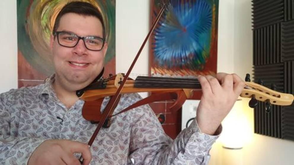 Stefan lindström håller en fiol i händerna. Han har glasögon och mörkt hår, fiolen är en el-fiol.