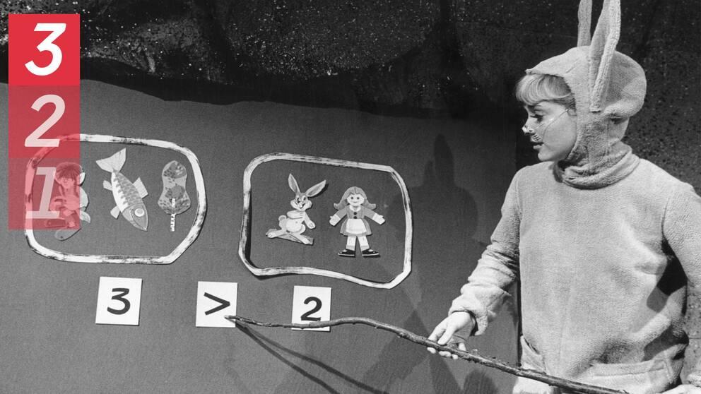 Skådespelaren Britta Pettersson utklädd till hare pekar på en flanellograf.