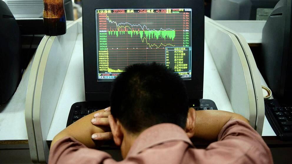 En handlare på Shanghaibörsen sjunker ihop framför sin skärm när kurserna bara faller. Bilden är från den 6 juli – i dag har kurserna dykt ännu mer. Shanghaibörsen föll nästan 7 procent vid öppnandet.