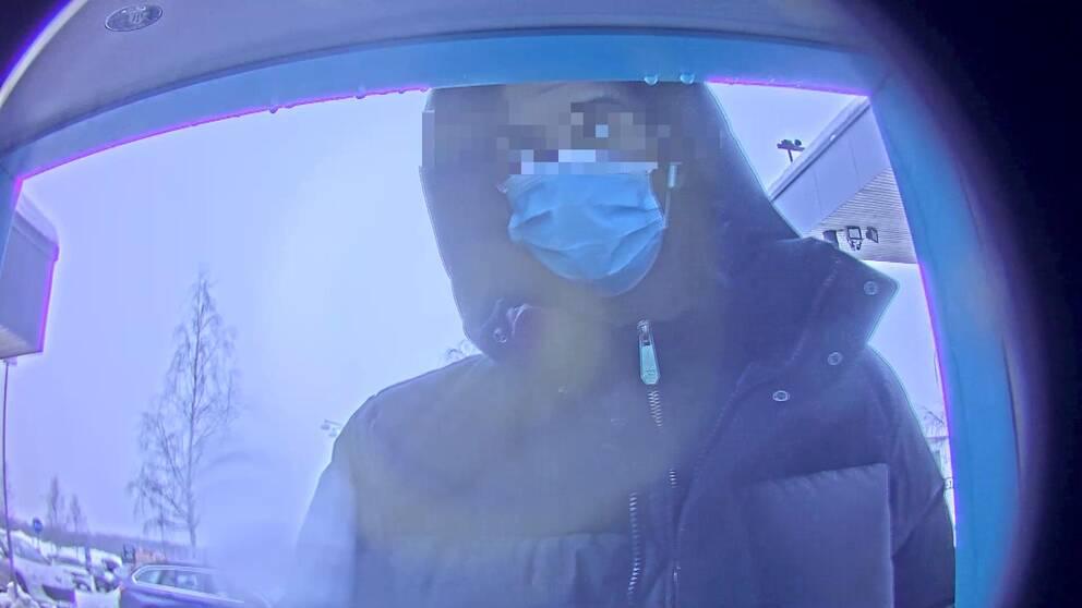 bild från övervakningskamera i bankomat – man ser en person med munskydd