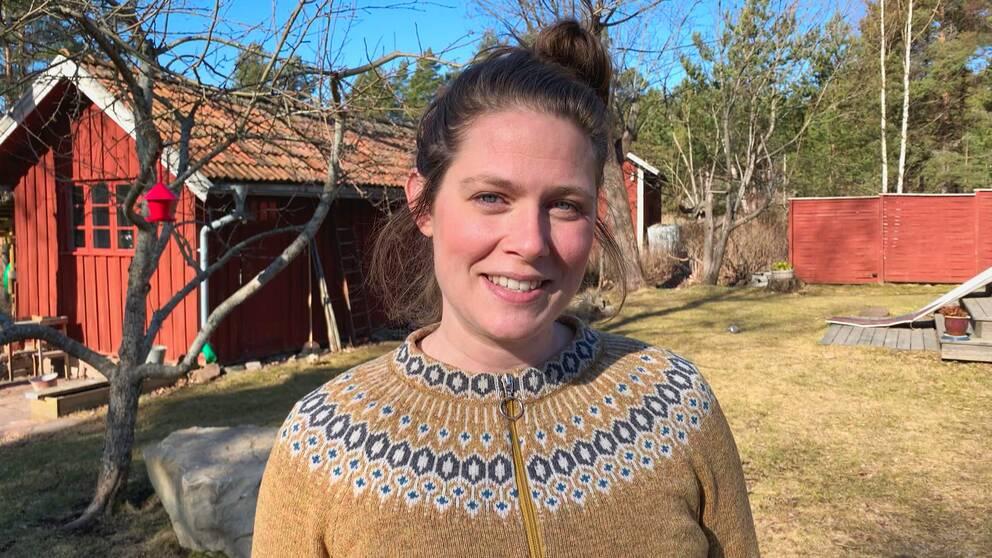 en leende kvinna i stickad tröja på en gård med trähus