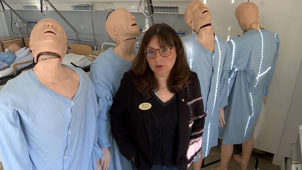 Maria står framför en rad med övningsdockor i naturlig storlek.