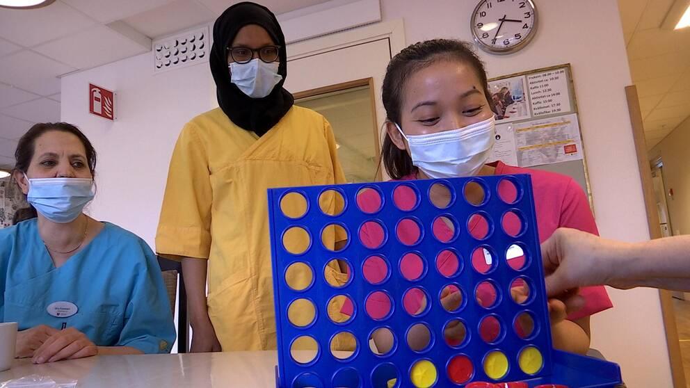 Tre kvinnor som arbetar på ett vårdboende hjälper en kvinna att spela fyra-i-rad.