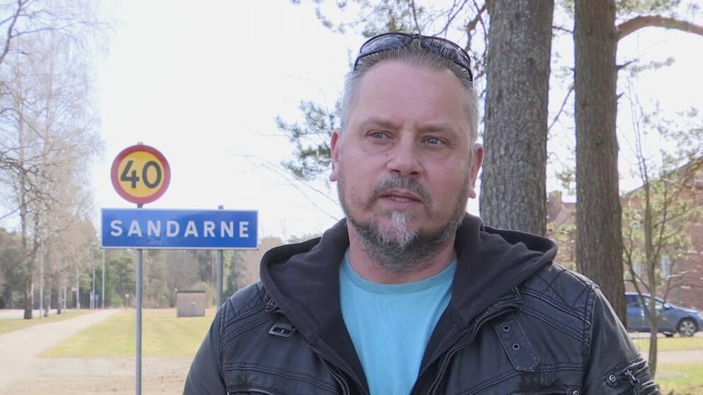"""en man som intervjuas utomhus vid en vägskylt för """"Sandarne"""""""