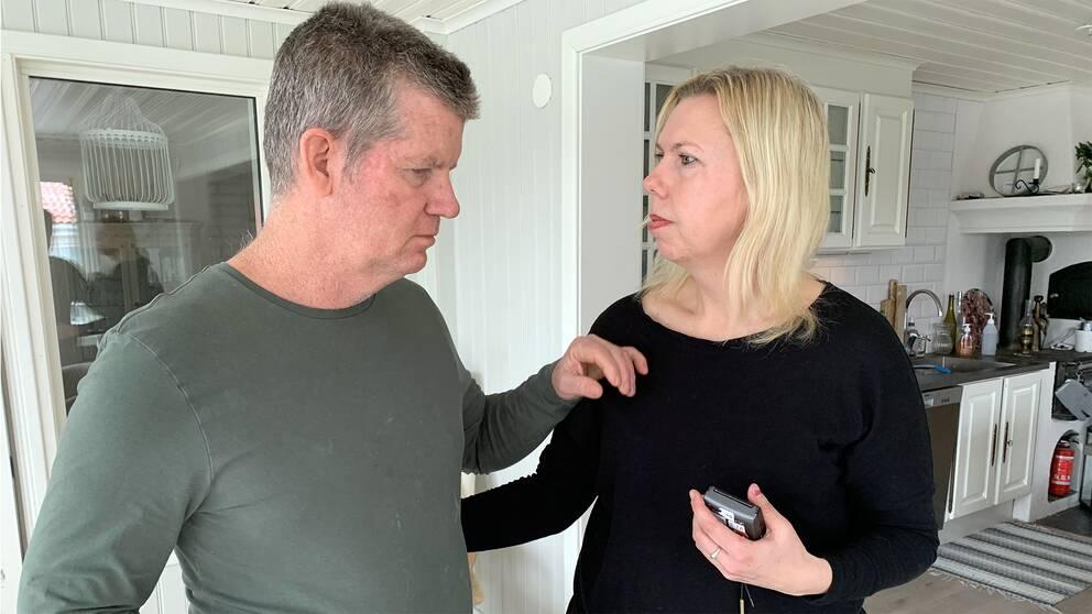 En man håller en hand på en kvinnas axel.