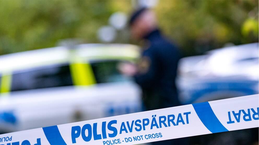 Bilden visar ett avspärrningsband samt en polis och polisbil i bakgrunden.
