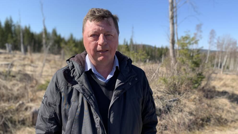 Politikern Ingemar Hellström (S) i Smedjebacken står framför skogen där en vindkraftspark ska byggas.