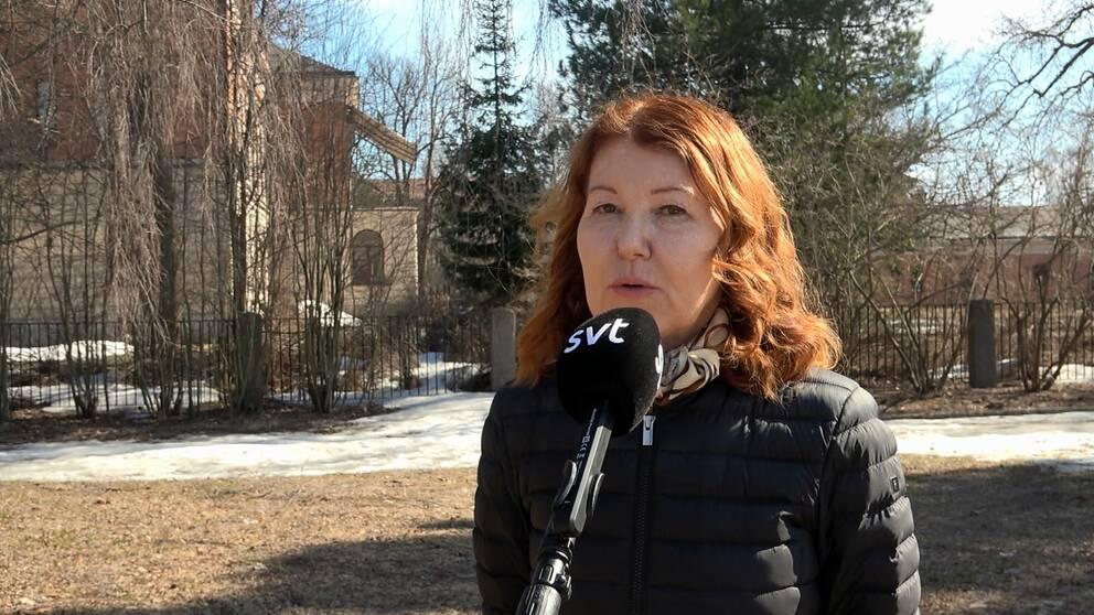 en kvinna intervjuas utomhus, träd och äldre byggnader i bakgrunden, snöfläckar