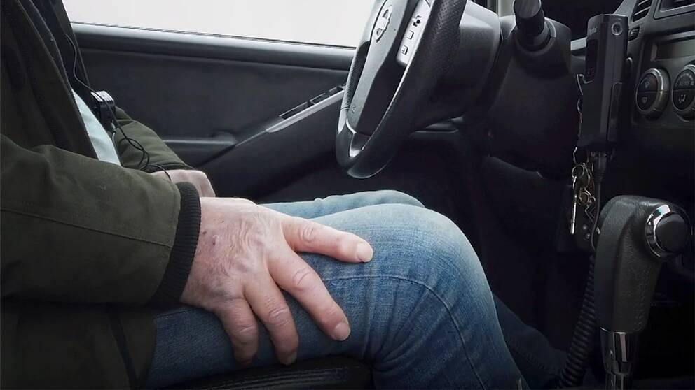 Man sitter med sin hand på knät i förarsätet på en bil.
