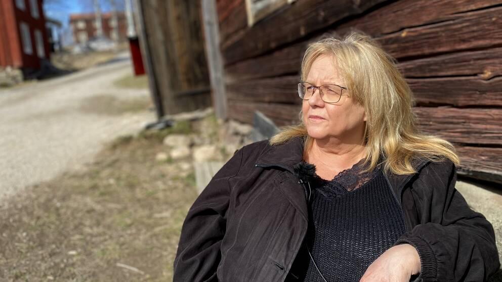 Lena sitter på en bänk i solen och tittar åt vänster.