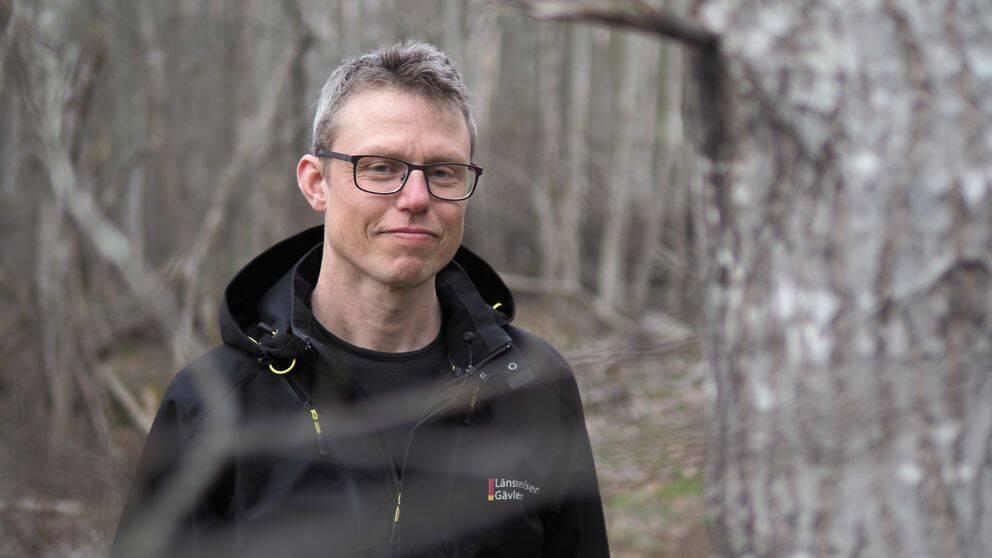 en yngre medelålders man med glasögon och jacka, fotad ute i skogen