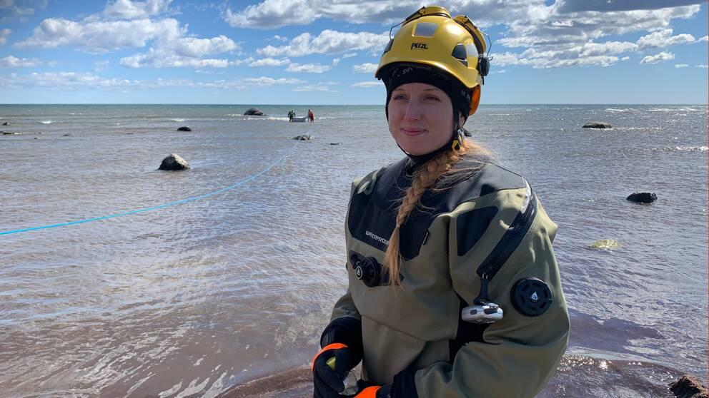 Bild på JasmineStavenow, biolog på SVA:s sektion för forskning och utveckling. Hon har på sig torrdräkt, handskar och en gul hjälm. Bakom henne syns havet.