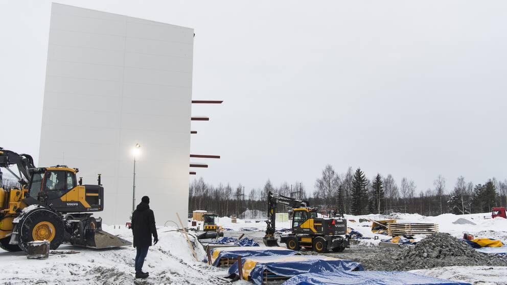 Två traktorer som jobbar med att bygga upp en ny fabrik. En stor vit vägg och en människa framför.