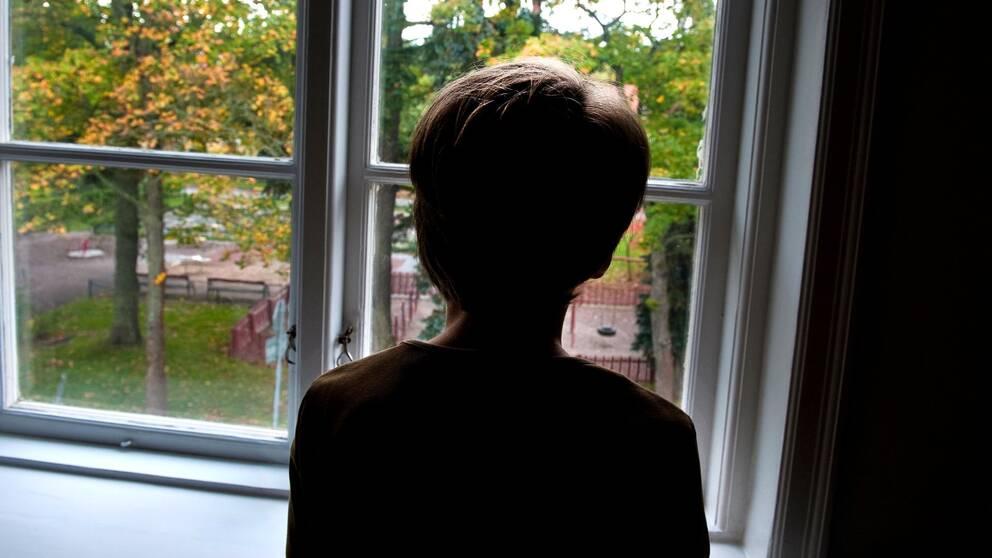 pojke som står och tittar ut från ett fönster