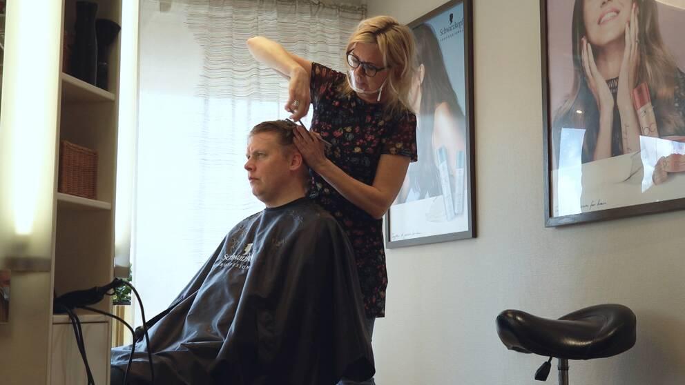 En frisör klipper en kund.