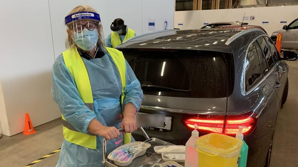 Kvinna med skyddsväst, visir och munskydd med en vagn med vaccinsprutor.