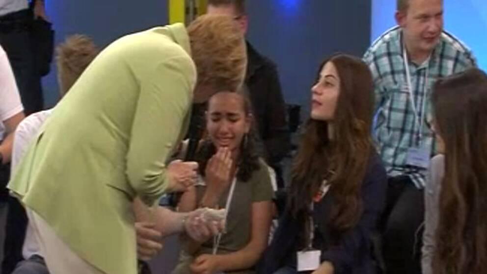 Merkel försöker trösta gråtande flykting flicka