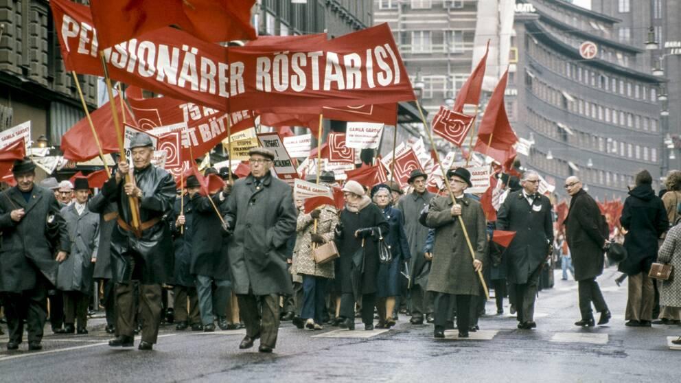 Första maj 1973. Socialdemokraternas demonstrationståg drar fram med fanor och banderoller längs Kungsgatan. Enligt SVT:s inrikespolitiska kommentator Mats Knutson är den vänsterlängtan som finns inom delar av Socialdemokratin förgäves. Arkivbild.