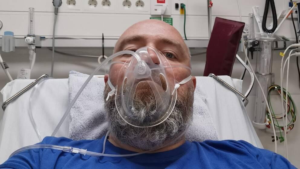 Man med blå t-shirt och skägg ligger i en sjukhussäng. Han tittar in i kameran.