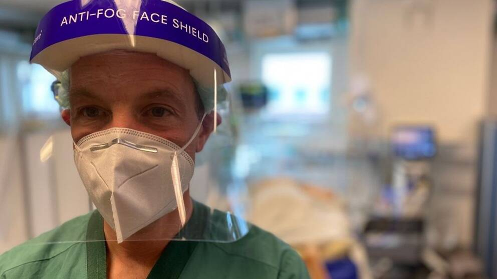 En person iklädd ett visir och munskydd.