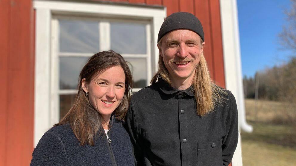 Matilda och Micke står längs med det röda huset med vita knutar och ler i solen.