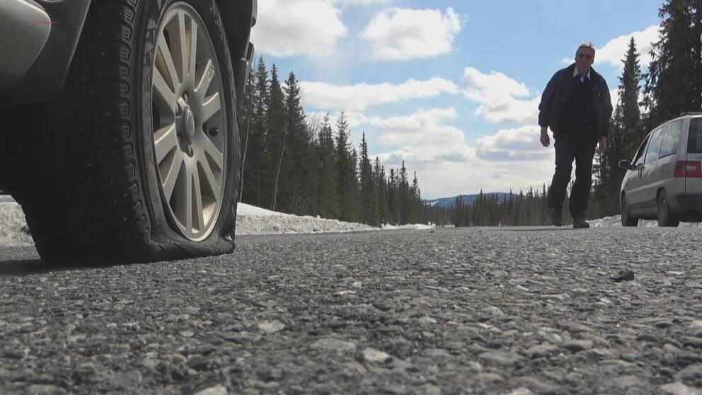 närbild på punkterat däck på en bil längs vägen, en person går i bakgrunden från en annan bil