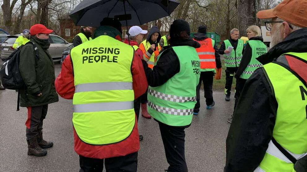 Bild på flera personer i gröna, orangea och gula reflexvästar. På ryggarna står det Missing People.