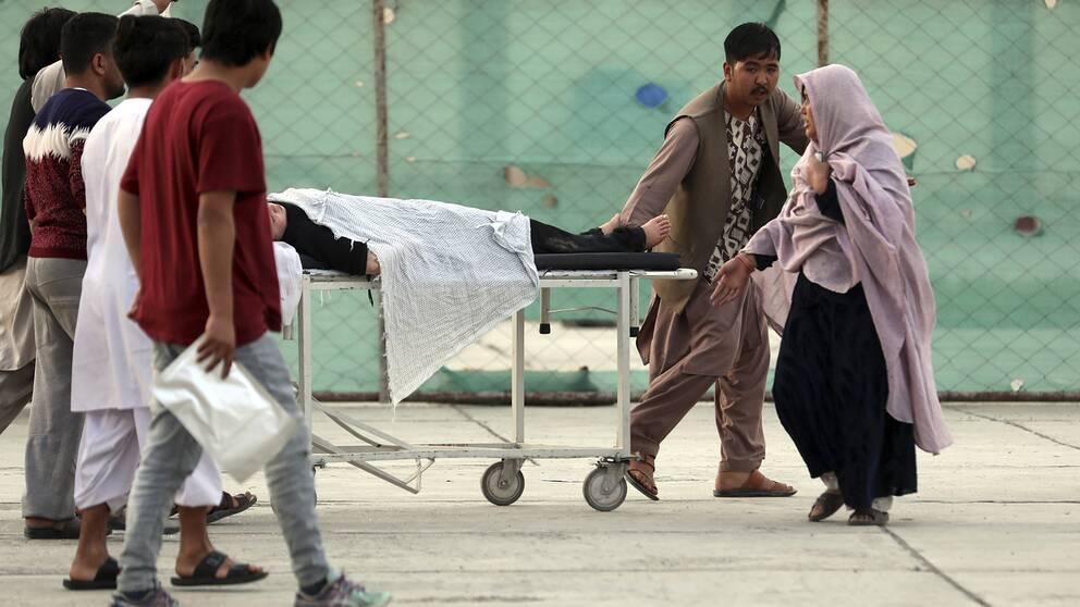 Människor drar en skadad person på en bår.