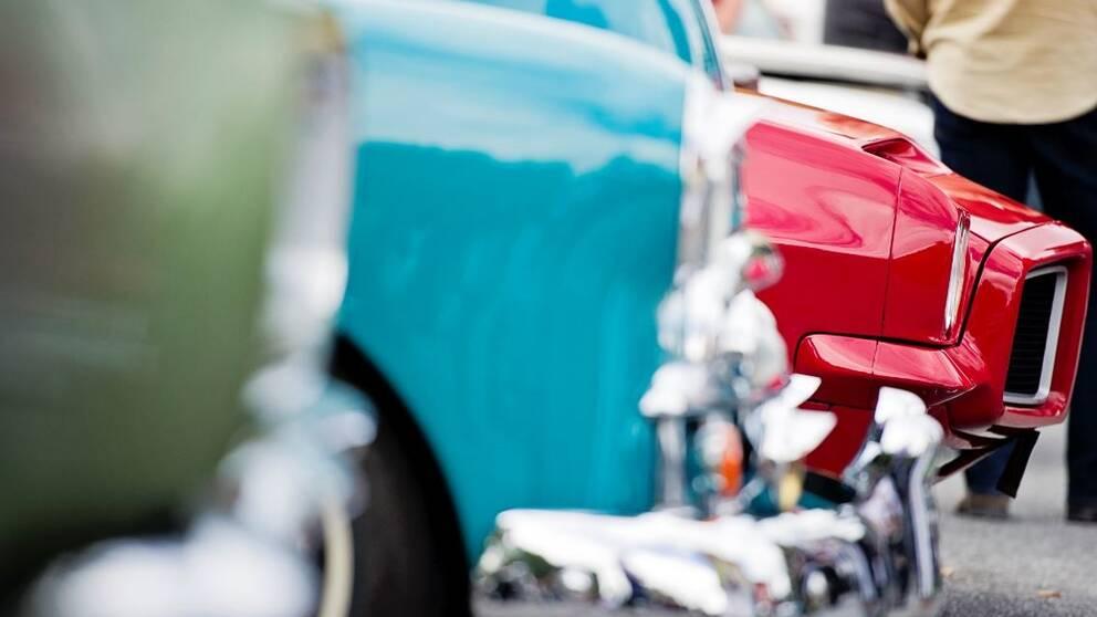Amerikanska fordon i glada färger syns i förgrunden. Man med ryggen mot kameran längst bort i bild.